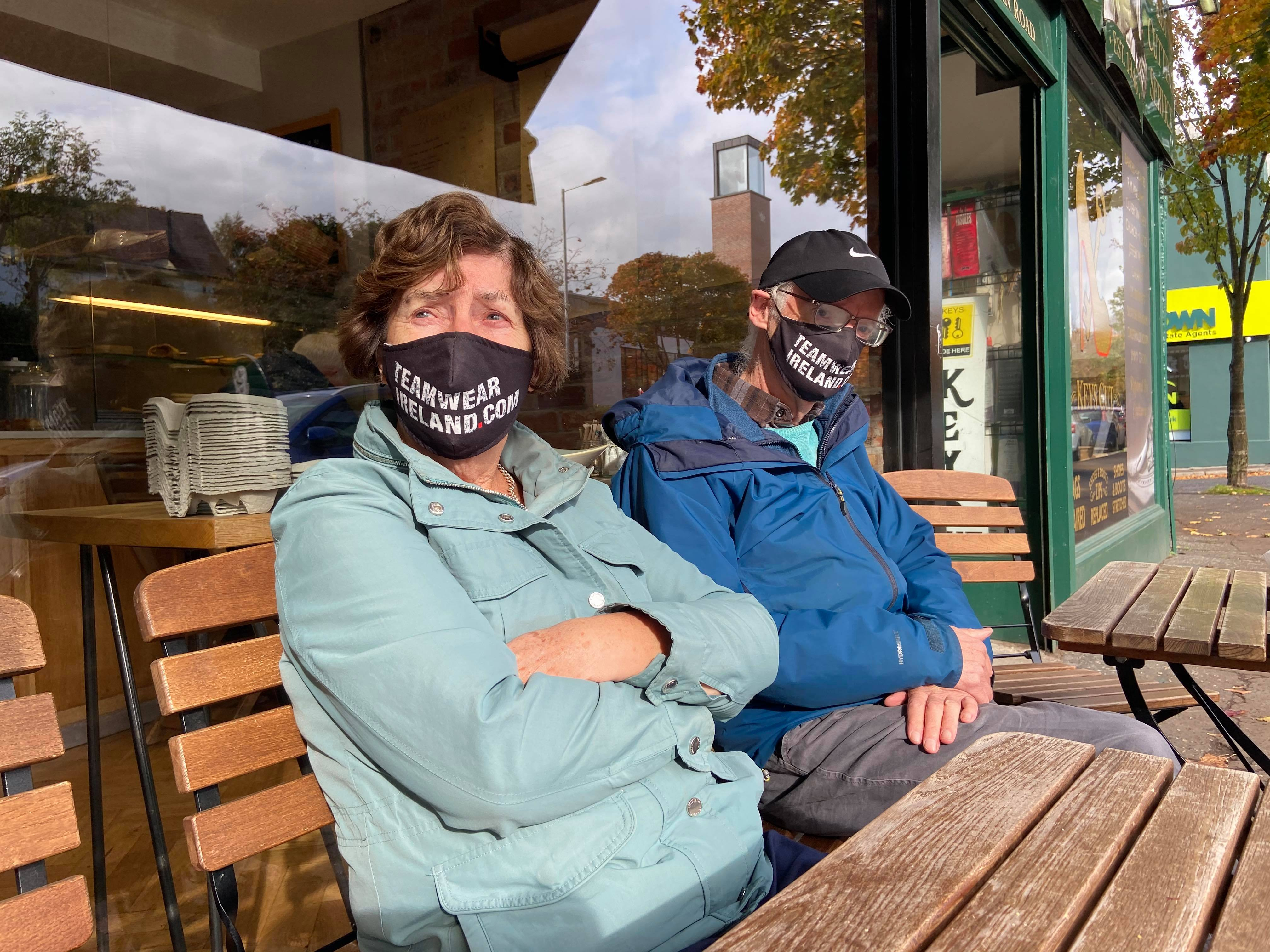 LOCKDOWN ON WAY: This couple outside a Belfast café were pictured just before the new lockdown protocols come into force at 6pm this evening