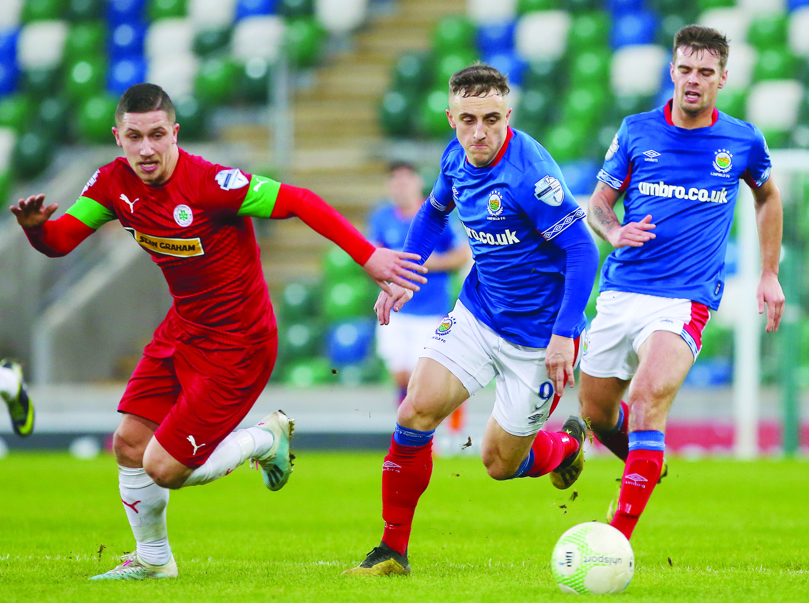 BATTLE: Linfield's Joel Cooper fights with Cliftonville's Seanan Foster for possession during last December's league game between the sides. The Belfast rivals clash once again this Saturday evening at Windsor Park