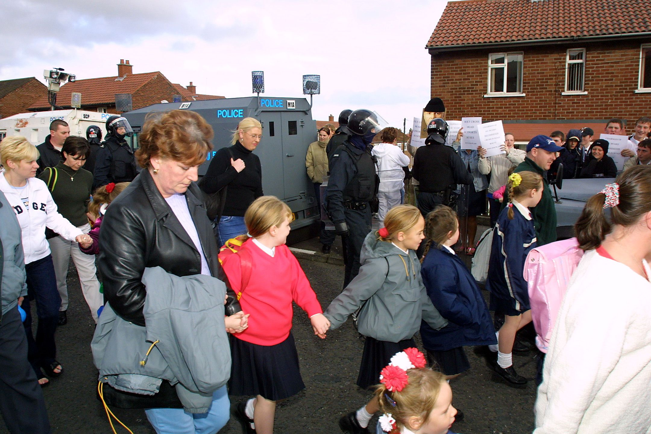 RUNNING THE GAUNTLET: Parents and children are escorted to Holy Cross Girls\' Primary School in 2001