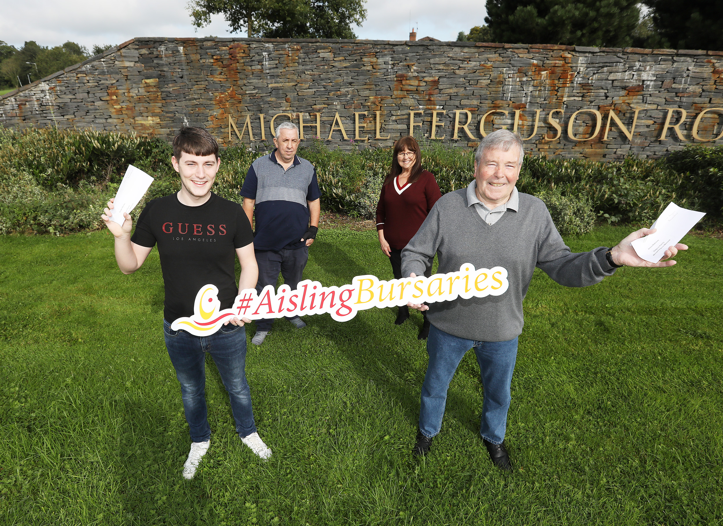Marie Toman and Stephen Ferguson presenting the Bursaries to Kaiden Norney, who is beginning a degree in Computing Technology at Ulster University, Jordanstown and to Jim Crystal accepting on behalf of Arlene McAreavey, who is studying Social Policy with Criminology at UU Jordanstown. .
