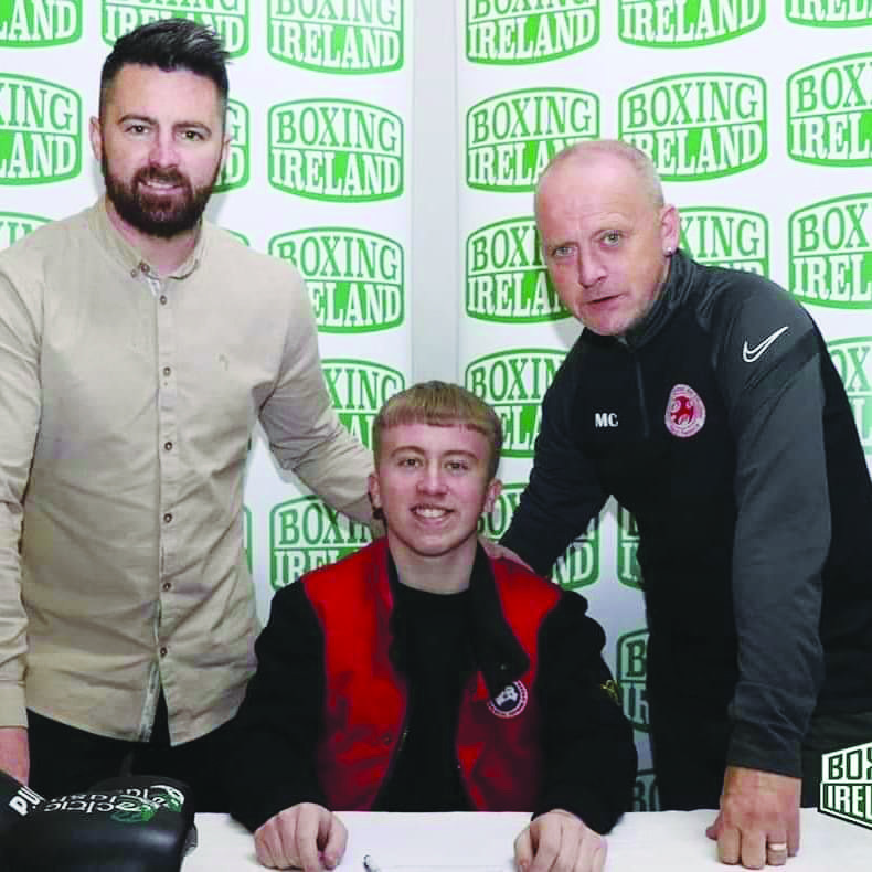 Michael Corr is flanked by Boxing Ireland's Dennis Morrison and his dad, Mickey Snr when signing his professional contract
