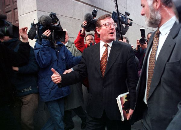 TOUGH TALKING: Flashback to April 1998 and David Trimble enters the Europa Hotel for a press conference carrying a copy of the Good Friday Agreement which his party has just endorsed.