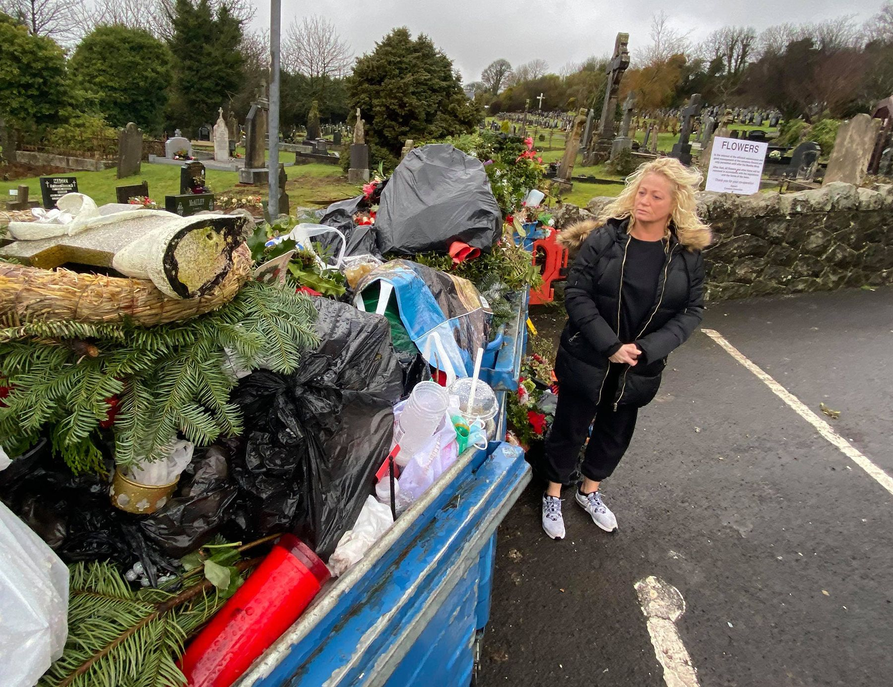 DUMPED: A distressed Michelle Connors at one of the skips loaded with flowers and ornaments