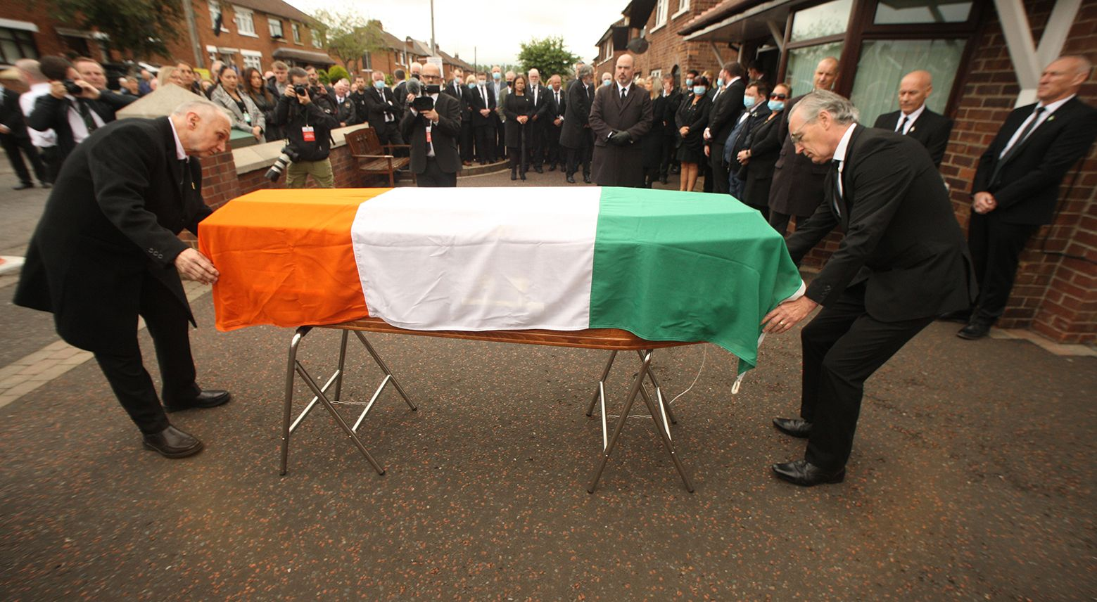 "FUNERAL HAS BECOME ""LIGHTNING ROD FOR UNIONISM\"": Seán Murray and Gerry Kelly MLA place the Tricolour on Bobby Storey\'s coffin."