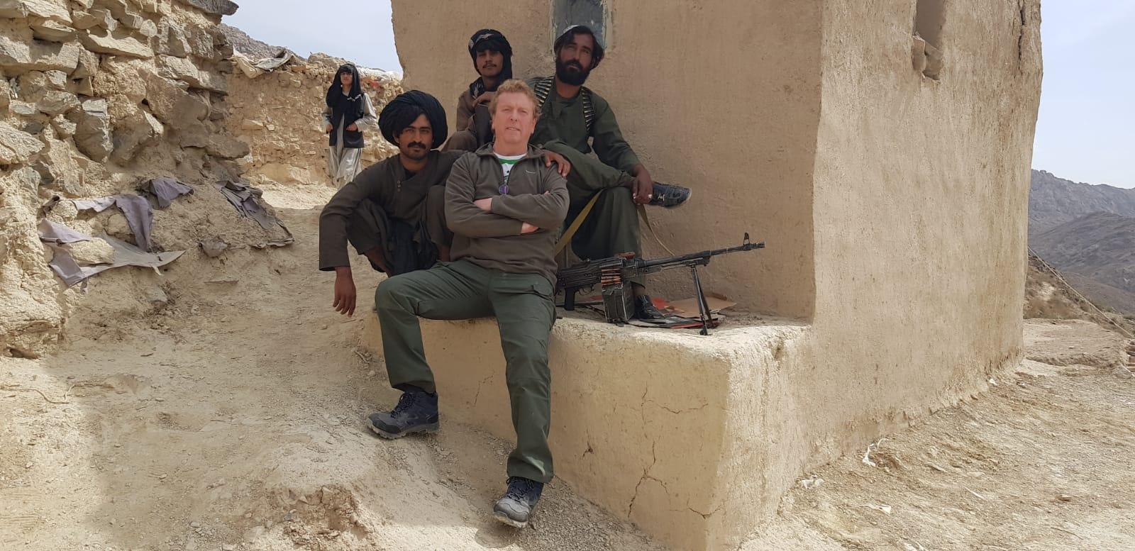 FOOTBALL FOCUS: Filmmaker Jamie Doran, sporting a Celtic top beneath his tunic, with his Taliban \'guards\'