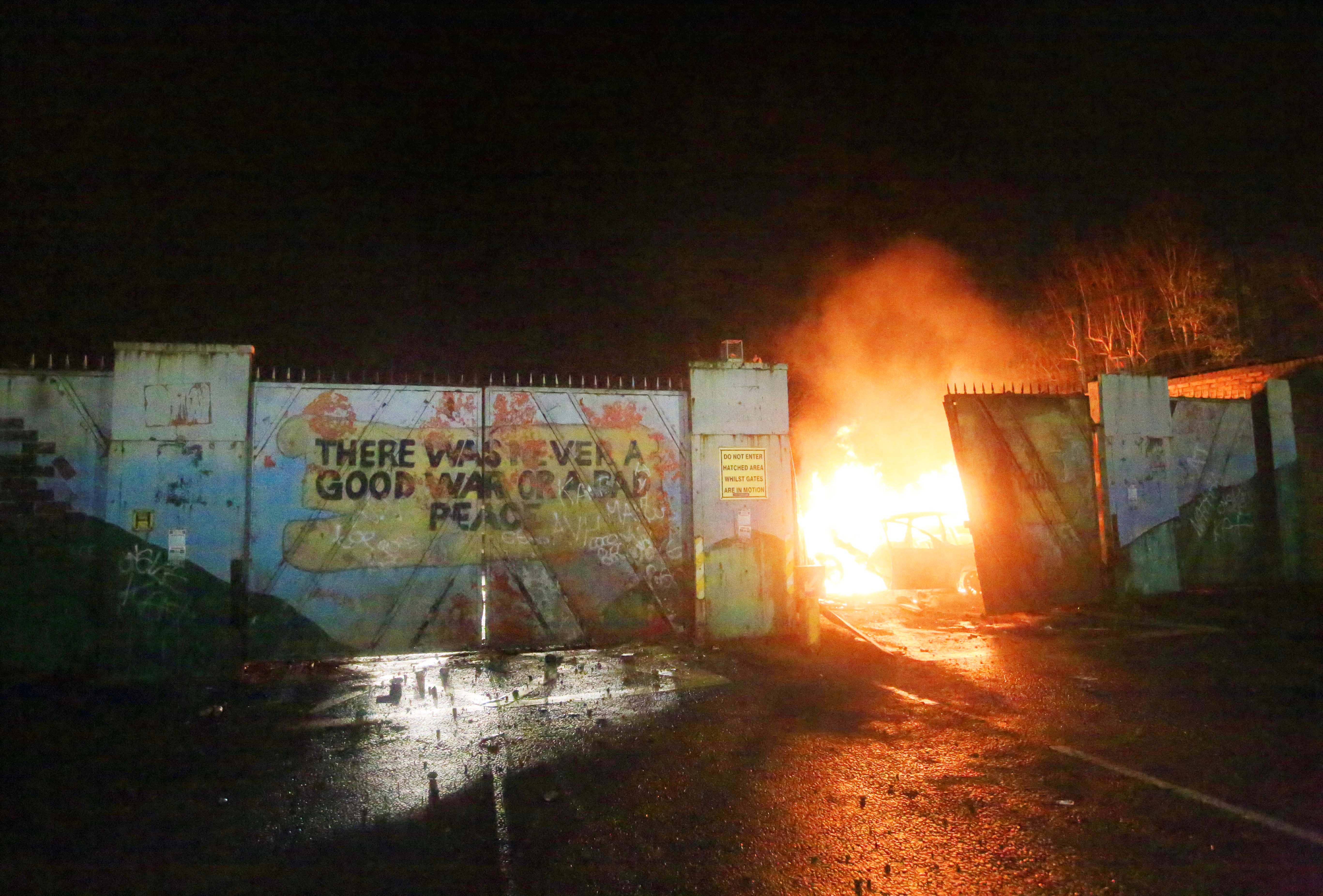 CAUSE AND EFFECT: A hijacked car burns on the loyalist side of the Lanark Way security gate