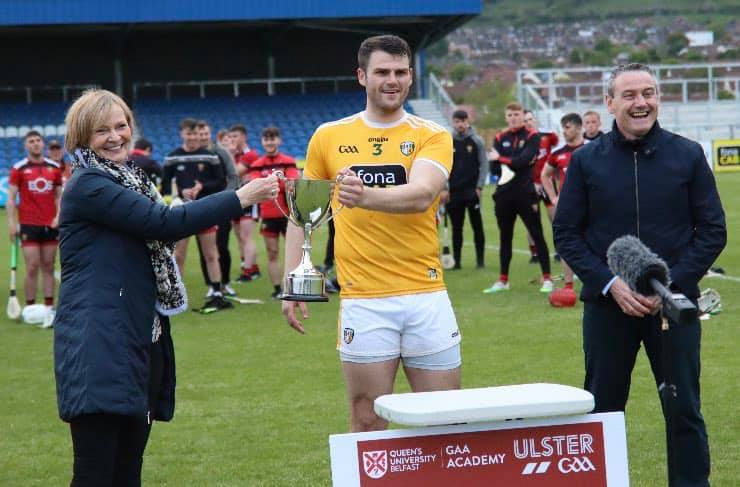 Antrim full-back Matthew Donnelly  accepts the Conor McGurk Cup from Paula McGurk and Ulster GAA Vice Chair Ciaran McLaughlin