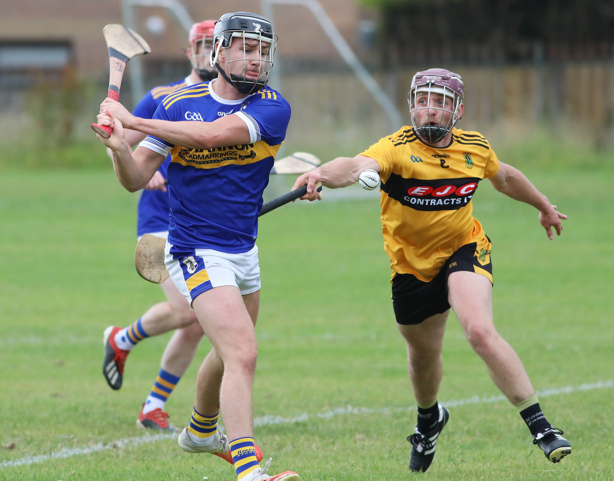 Rossa\'s Dominic McEnhill gets his pass away despite the close attention of Naomh Éanna defender Matthew Donaghy