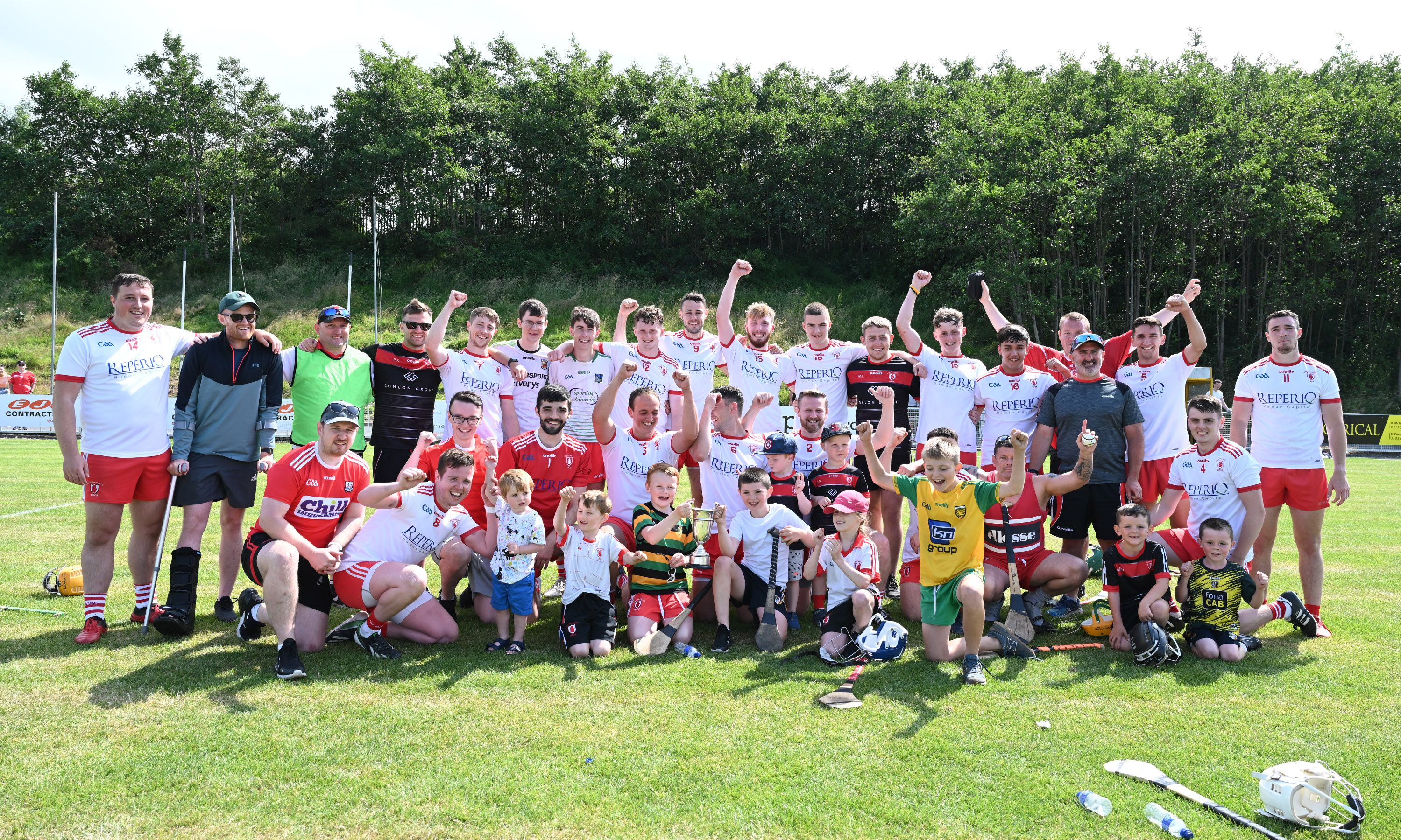 Lámh Dhearg players celebrate with the Division Four trophy at Hightown on Sunday