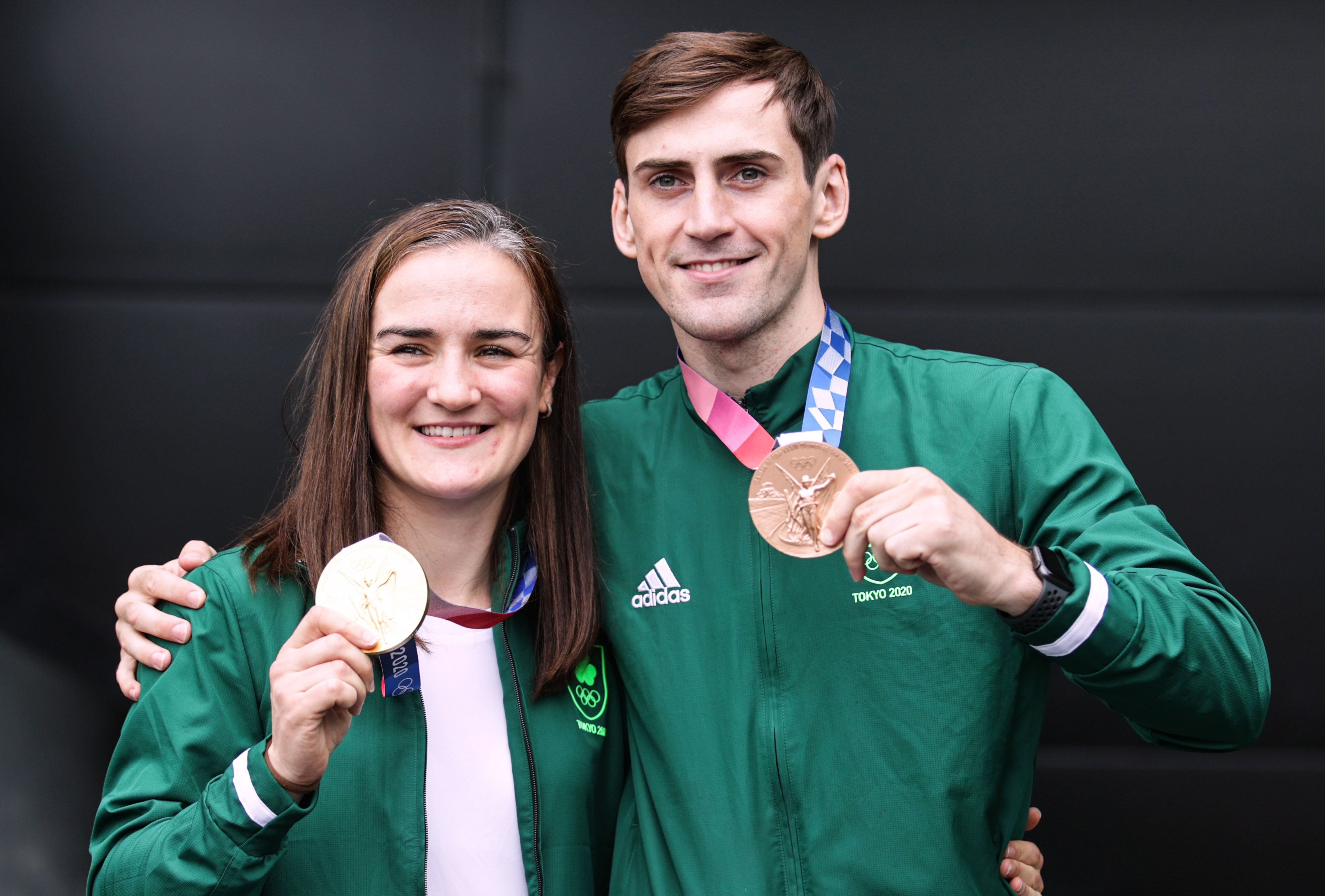 Kellie Harrington and Aidan Walsh show off their respective gold and bronze medals at Dublin Airport yesterday