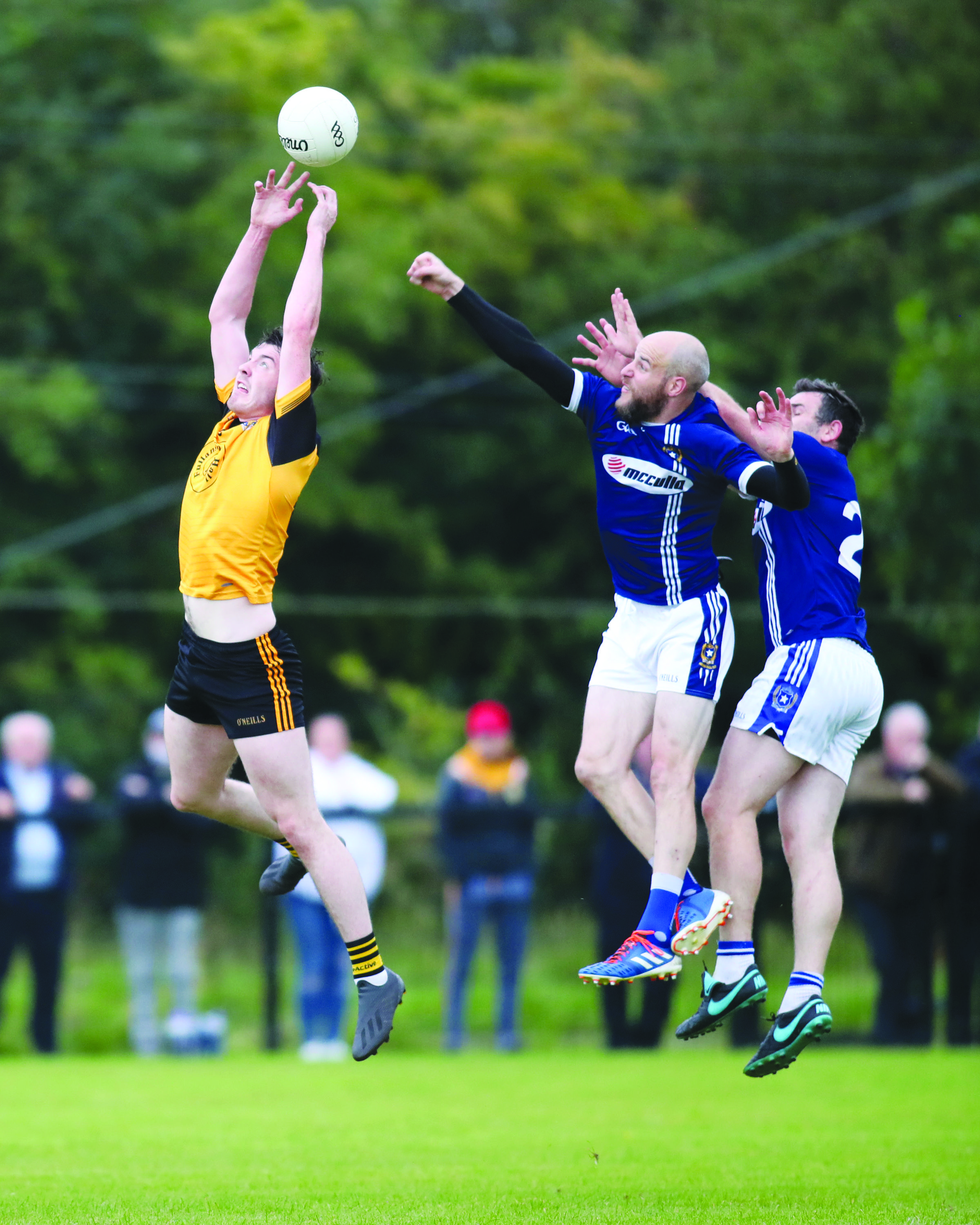 Fergal O'Kane gets up above Aodhán Gallagher and Sean Burke