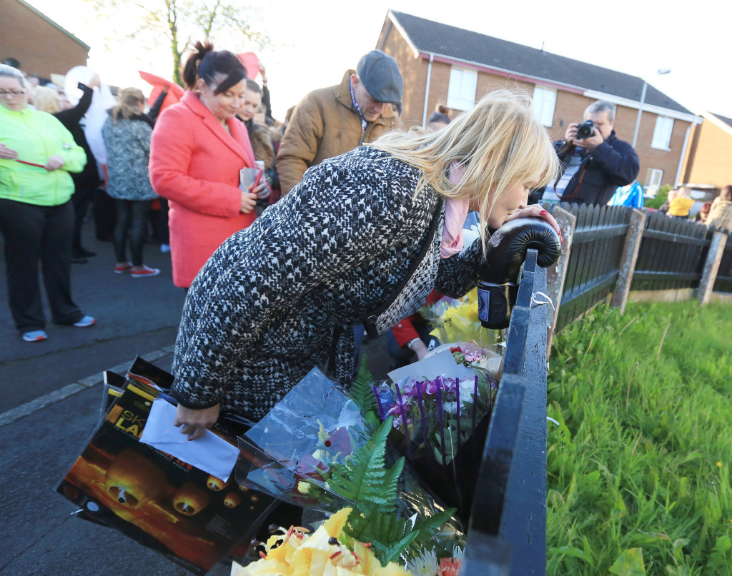 Eamonn Magee Jnr's mother Mary kisses a single boxing glove left near the scene of the killing while his dad Eamonn Snr bows his head. Pic by Jim Corr