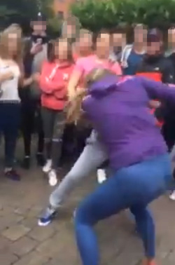 The girls, one from Lenadoon and one from the Shankill, attack each other in a circle formed by a crowd of youths