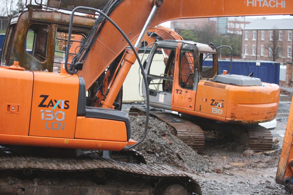Burnt-out diggers at a North Queen street housing development – one of several sites where work has ceased after AAD extortion demands