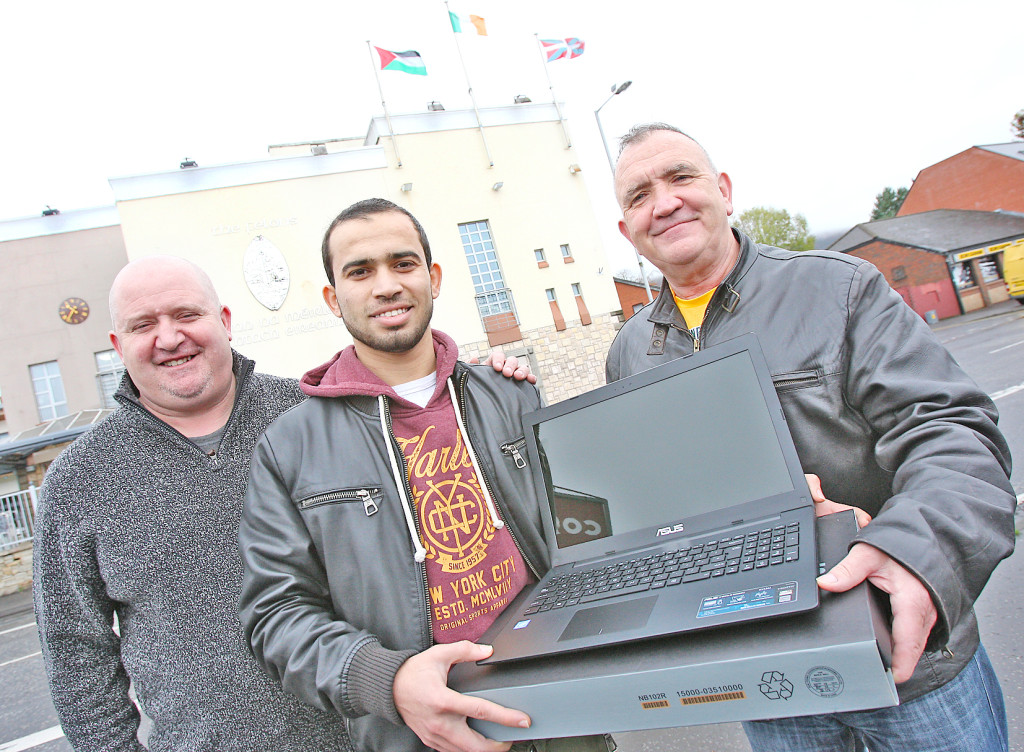 Gerry Scullion of the Felons presents Mustafa Afana from Palestine with a laptop for use in his studies at Queen's. Looking on is local photographer John Mallon