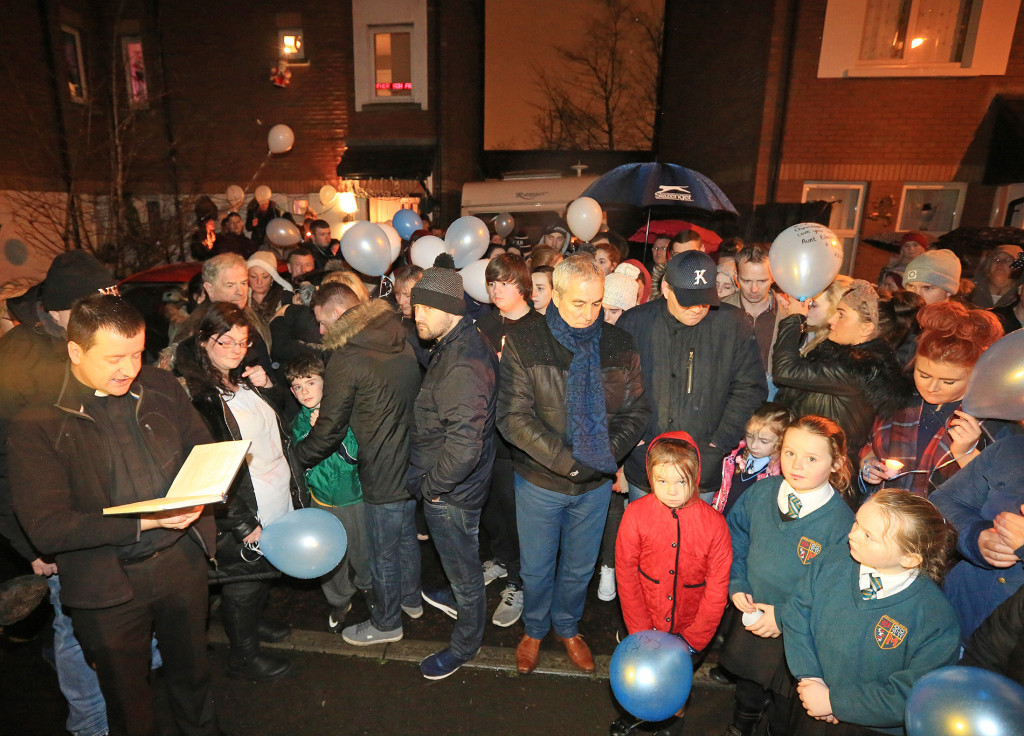 Father Darach Mac Giolla Catháin reads prayers at the vigil; on his left are Christopher's parents Chris Meli and Vanessa Burke with one of their younger sons     Pic by Jim Corr
