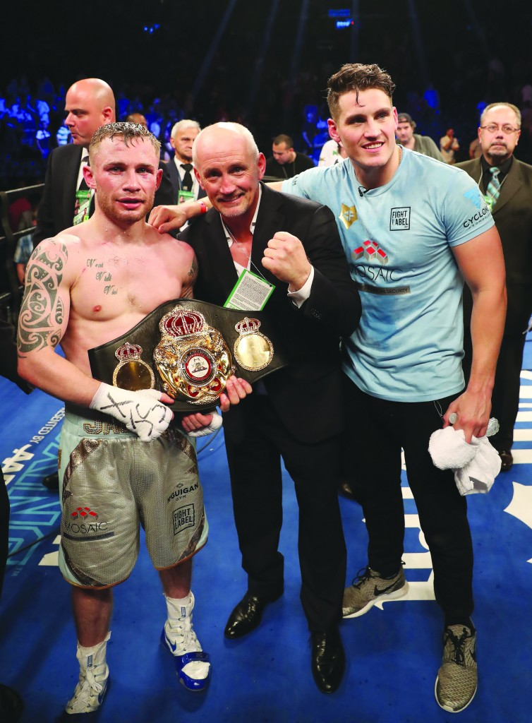 Carl Frampton, Barry McGuigan and Shane McGuigan pose with the WBA featherweight title belt after 'The Jackal' made history by becoming the first two-weight world champion from the North in Brooklyn on Saturday night