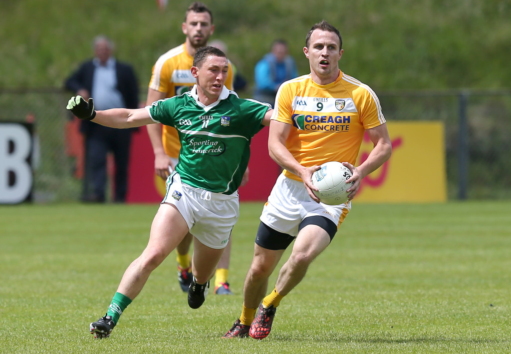 Michael McCann, pictured in action against Limerick's Peter Nash during Antrim's Qualifier defeat at Corrigan Park in June, insists he hasn't retired from inter-county football despite opting off the Saffron squad for the forthcoming season due to work commitments