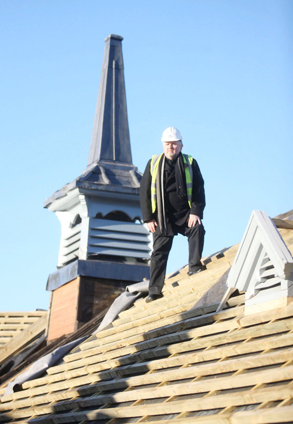 Fr Gary on the roof of the Houben Centre during its refurbishment. It has since been revealed the builders carrying out the work were approached for protection money