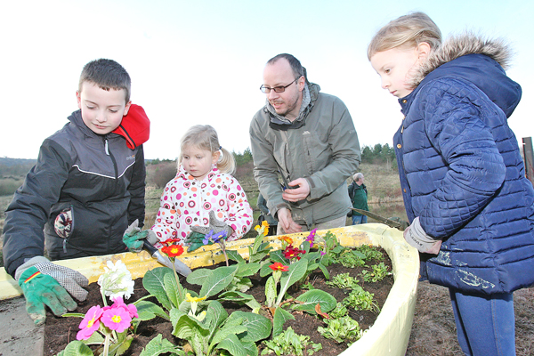 Seamus Armstrong and his children, Sophie-Belle, Lucy and Dylan planting flowers at Colin Glen Forest Park in memory of mother and wife, Valerie Armstrong