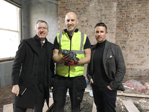 HOLD-UP: Máirtín Ó Muilleoir MLA, Neil Skillen of pest controllers Termapest Ltd, and Anthony Kieran, owner of UsedcarsNI.com at the Upper Crescent property where essential restoration work has been held up by Council regulations