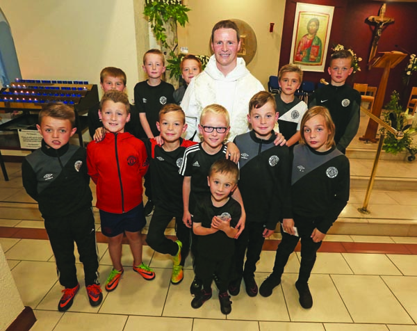 LOCAL TEAM: Fr Philip Mulryne with boys from Oliver Plunkett FC