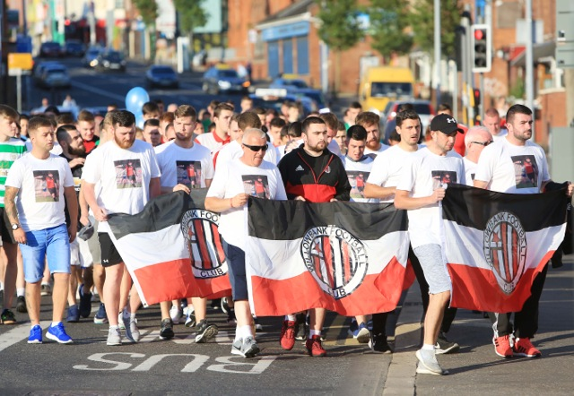 James' friends make their way down the Falls Road to remember the much-loved soccer coach