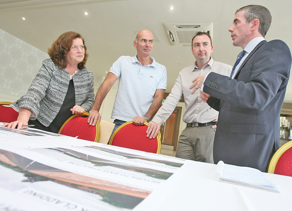 Simon Wells, Engineer at Aecom, speaking with Cllr Geraldine McAteer, Jim McCann and Jim Girvan over the new bridge options that are now available to view