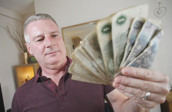 FIND: Paddy McCann with the old notes he discovered in a wallet in his Ardoyne home