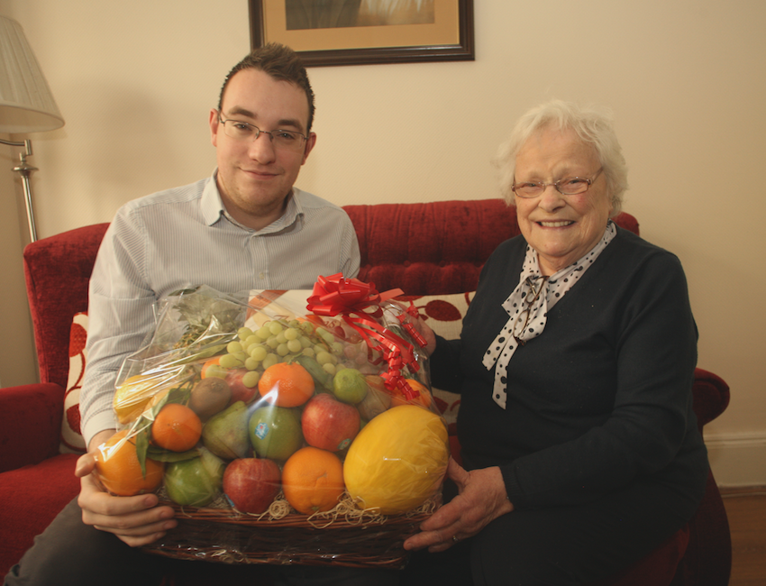 KIND-HEARTED:Conor McParland from the North Belfast News hands over a Christmas hamper to Olive McAlea that was donated by a local businessman\n\n\n\n