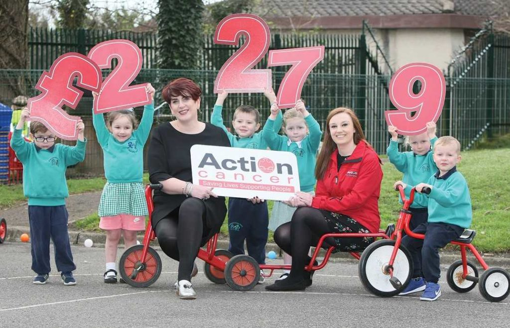 Mrs Clare McAllister, principal of St Michael's Nursery School, and pupils Ryan Lavery, Aishlinn Killen, David Killyeagh, Niamh O'Hagan, Orlaith Ferry and Cillian Ferry, present Madeline Knowles, fundraising executive from Action Cancer, with £2,279 after the children participated in a sponsored cycle at their school