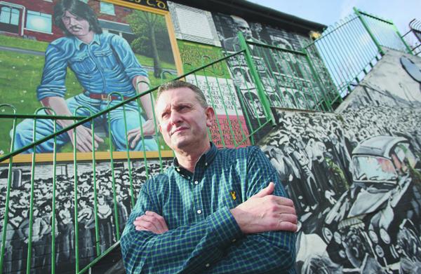 \nHISTORY:Seamus Kearney beside an Andersonstown mural tribute to hunger striker Kieran Doherty