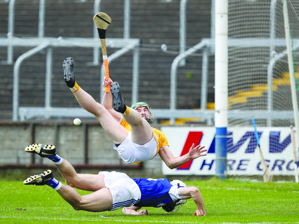 Antrim captain Conor McCann, pictured following a collision with Laois defender Joe Phelan in their Joe McDonagh Cup round two clash, expects another tough battle when the Saffrons take on Offaly in O'Connor Park, Tullamore on Saturday afternoon