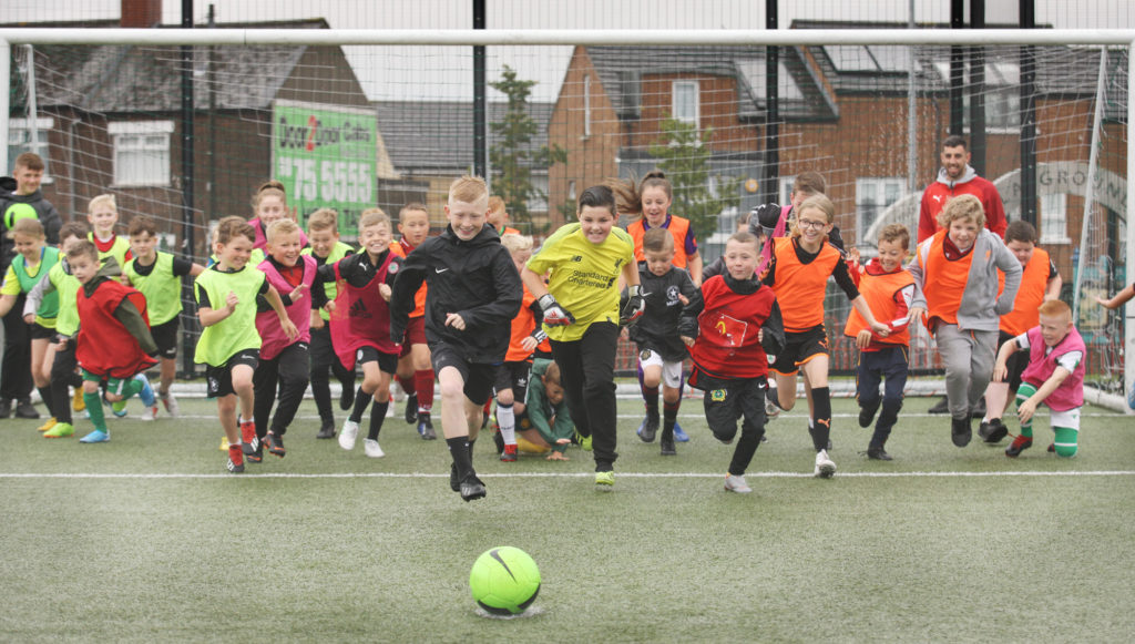 Children at the Ardoyne and Bone Community Festival Mini World Cup held at the Marrowbone Millennium Park with Joe 'the Goal' Gormley of Cliftonville FC