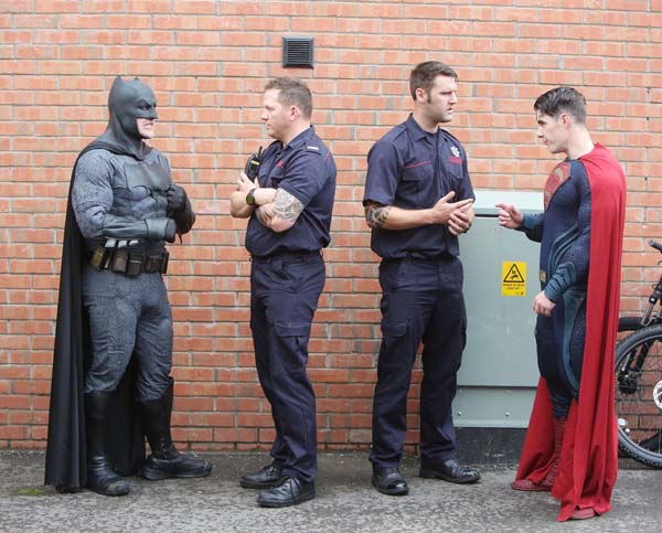 Real heroes meet fantasy heroes as firefighters chat with Batman and Superman at a community event in the New Lodge