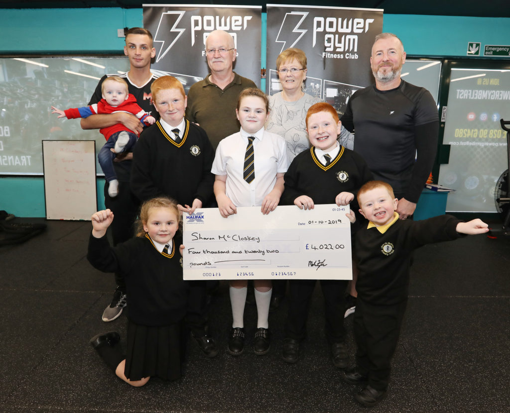 The parents of West Belfast's 'Sunflower' Sharon McCloskey thank the community for all their fundraising efforts including staff and management from Twinbrook based Power Gym who held a white collar event in the Devenish Complex. Pictured are: Sharon McCloskey's parents John and Alice Whyte, Sharon's sons Joshua, Matthew and Caleb, also pictured are Charlotte and Grace Dunne and Power Gym's Ciaran Cunningham and Mathew Fitzsimons