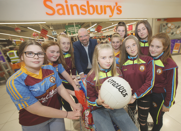 Kennedy Centre Manager John Jones donates some goodies to Gort na Móna girls footballers for their Christmas party