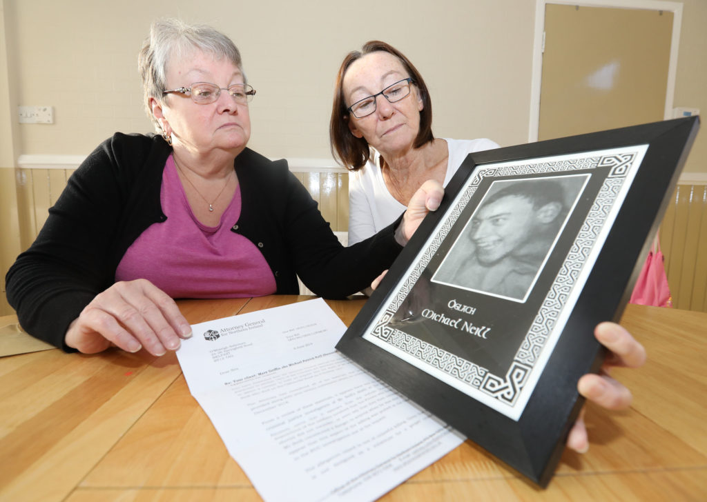JUSTICE: Maureen Griffin and Patricia Friel with a treasured portrait of their brother Michael Neill