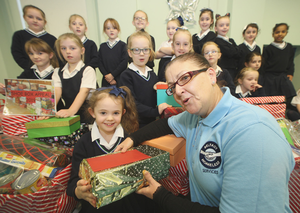 Jessica Mooney and her P4 class from Our Lady's Girls' Primary School present Liz Rocks of Belfast Homeless Services with food and clothing, donated from their Shoebox Appeal