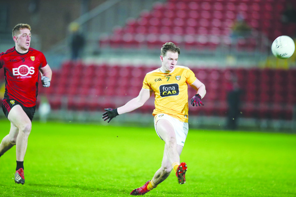 Antrim defender Peter Healy clears his lines as Down midfielder Seam Dornan closes in during Wednesday night's Dr McKenna Cup clash in Newry. The Mournemen eased to an eight-point victory to book a semi-final meeting with holders Tyrone this Sunday