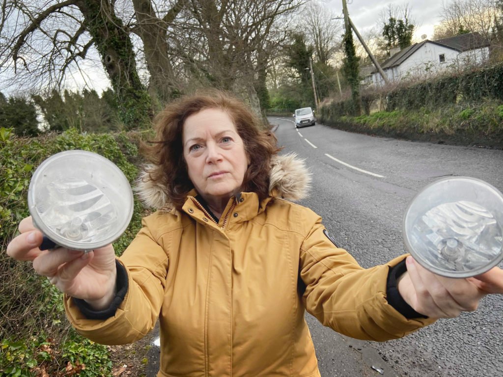 BLACKSPOT:Cllr Geraldine McAteer holding lights from cars that have had accidents at the bend in Dunmurry