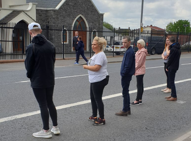 RESPECT: Staff from Brooklands and local youth volunteers applaud the funeral cortege of resident Isabell Moreland (see video below)