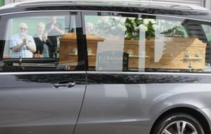 Applause from mourners lining the road as the funeral cortege of John Thomas passed by[/caption]