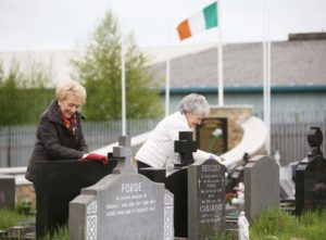 PAYING RESPECTS: Sisters Jo and Alice Quinn who are self-isolating together tidy relatives' graves at Milltown Cemetery on Sunday.