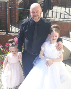 SLAIN: Kieran Wylie with granddaughters Maddison and Mya at a First Holy Communion celebration. (Photo with kind permission of the Wylie family.)
