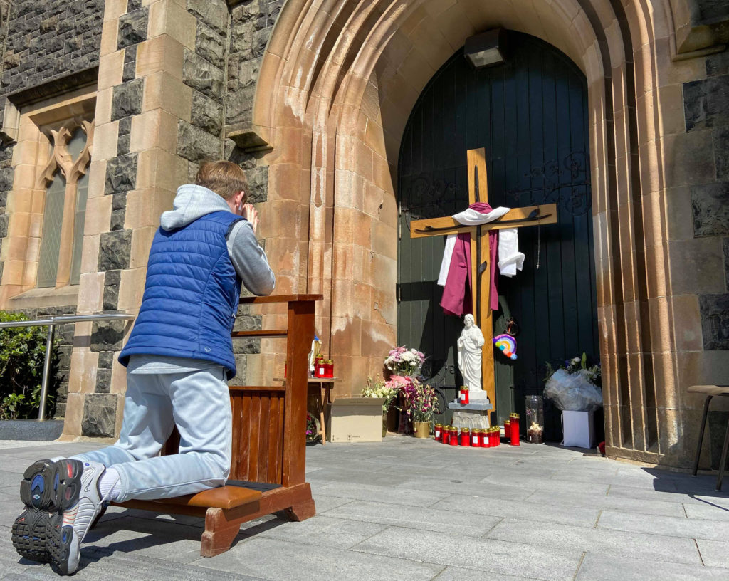SACRIFICE: A cross and religious items have been placed at the door of St Teresa's Church on the Glen Road which has been closed due to the Covid-19 Crisis.