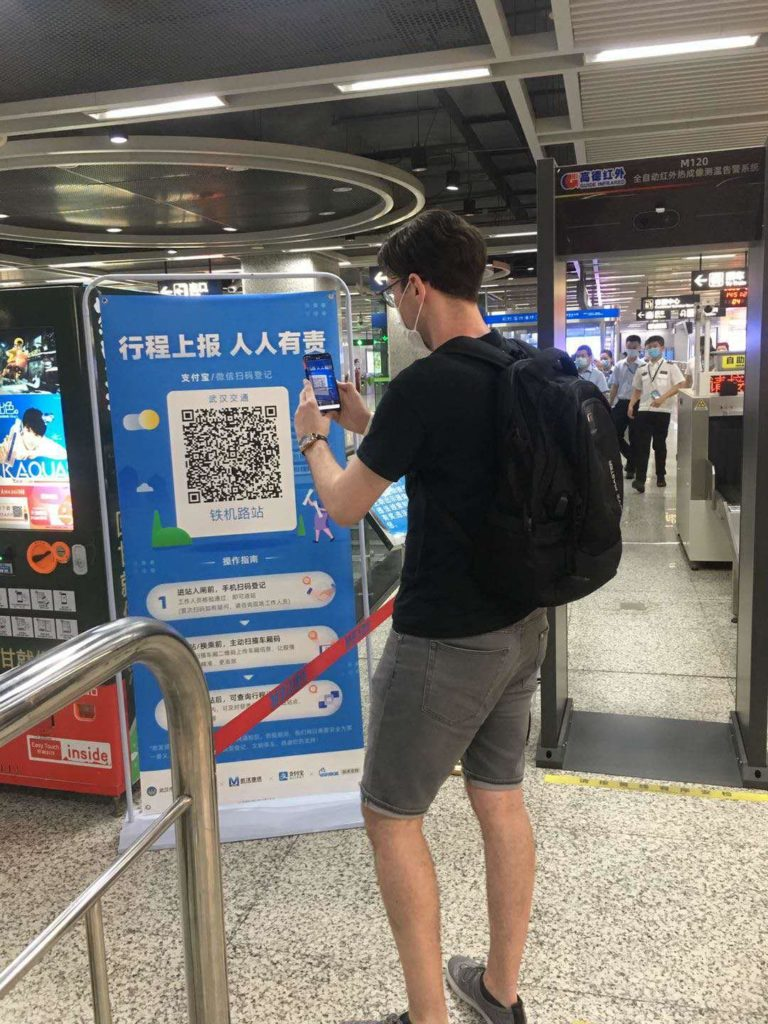 SELF-MONITORIING: Seán Ó Garmaile scans in the QR code from his smartphone before getting on the metro in Wuhan. The metal detector-style portal beside Seán checks his temperature.